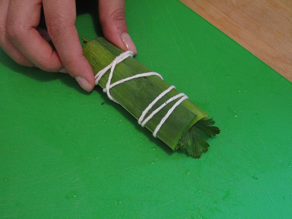Cut about 16 inches of kitchen twine with scissors, and wrap the twine around the packet.