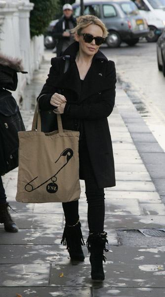 Kylie Minogue working all black on the streets of London. Loving that adorable safety-pin tote, too.