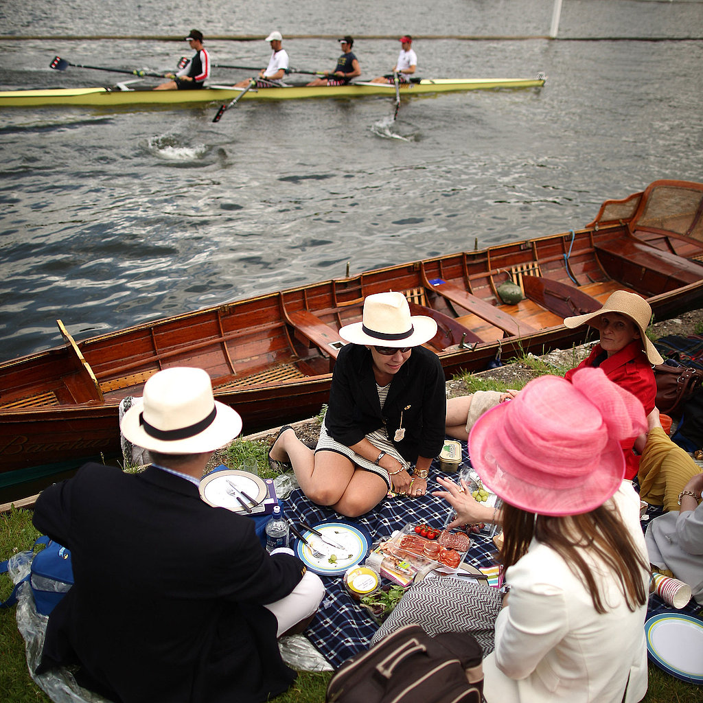 Spectators snack along the River Thames as a crew rows by.
