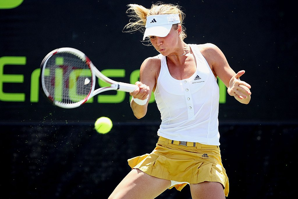 Maria Kirilenko looked sporty yet chic in Adidas by Stella McCartney in her white button down, sleeveless shirt tucked neatly into her belted yellow leather skirt.