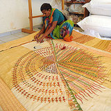 An Indian woman stitches an intricate quilt.