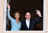 Princess Charlene of Monaco and Prince Albert II of Monaco wave from the balcony.