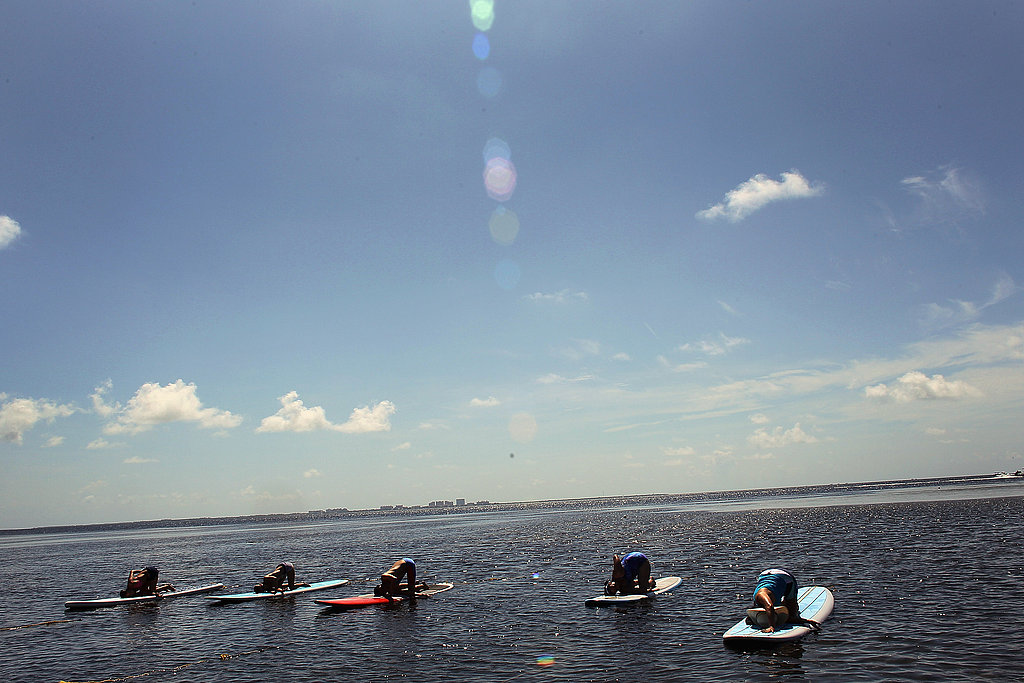 Yogis participate in a paddleboard yoga session.