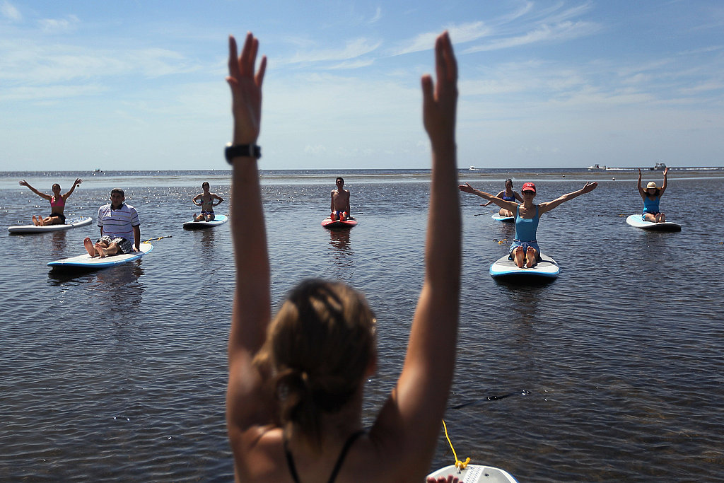 A yoga instructor leads a paddleboard yoga class in Miami.