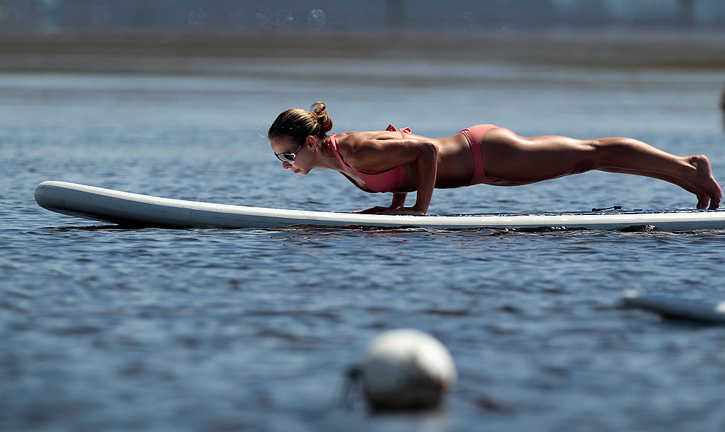 A paddleboard yoga participant works out on the water.