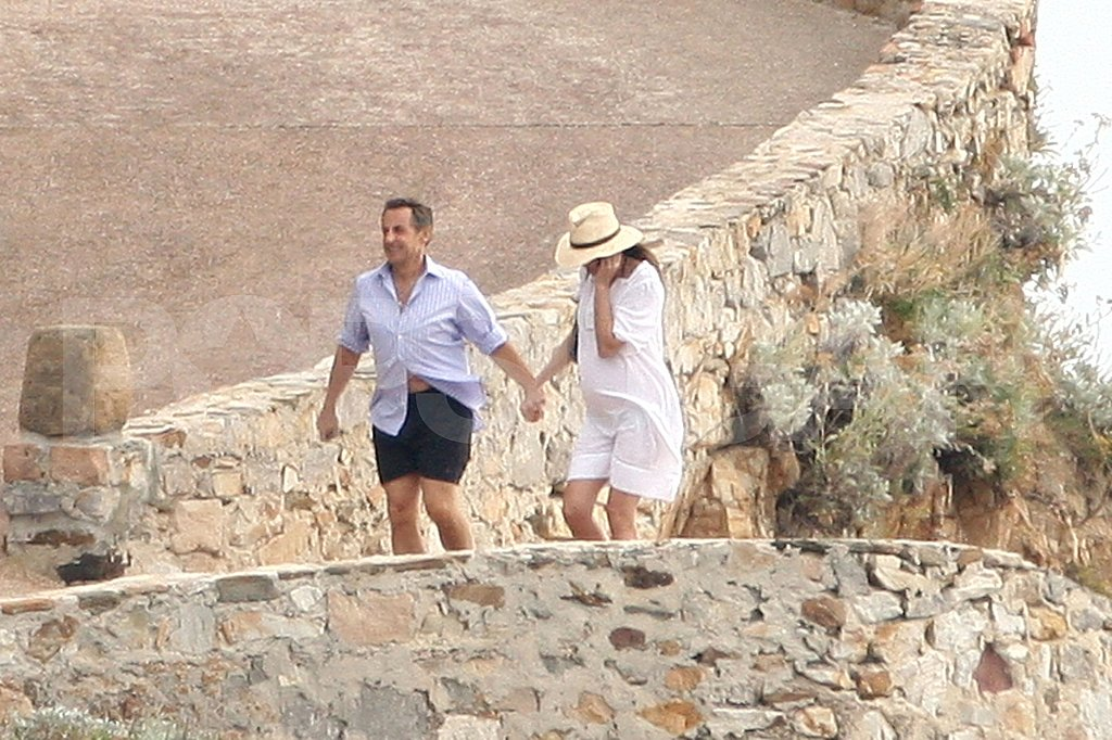Carla Bruni-Sarkozy and Nicolas Sarkozy hold hands on a walk.