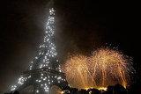 Bastille Day fireworks shower the sky alongside a the Eiffel Tower.