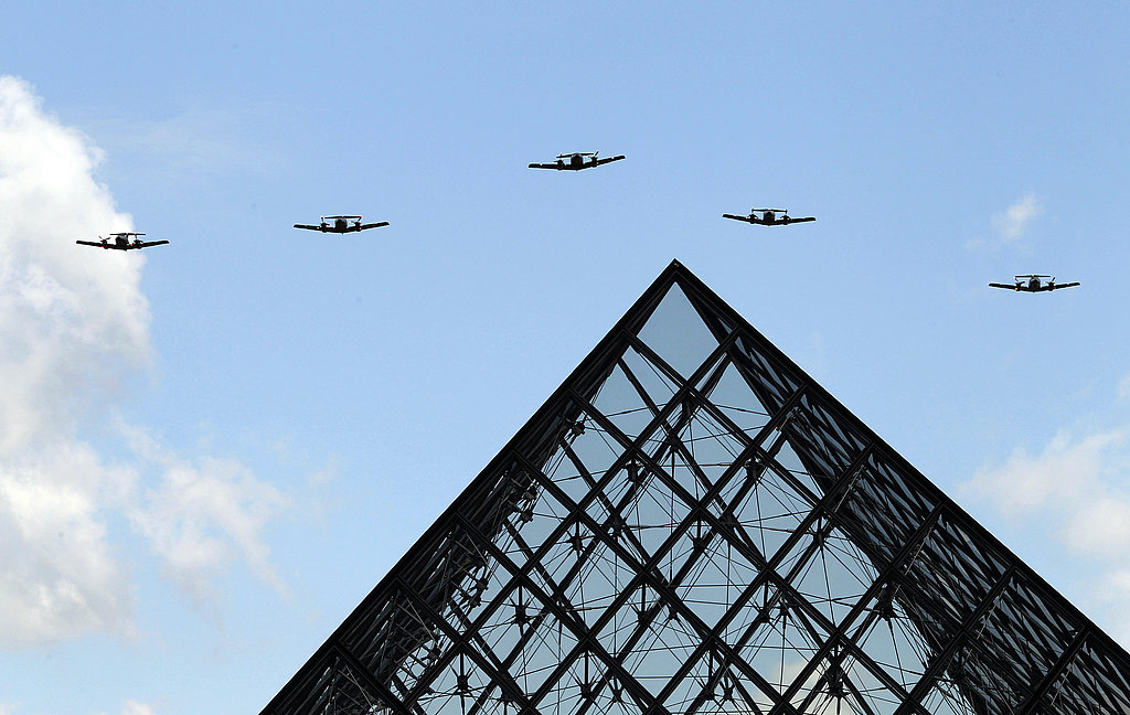 French military planes soar over the Louvre Pyramid during the Bastille Day parade.