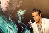 Ryan Reynolds posed in front of a Green Lantern poster.