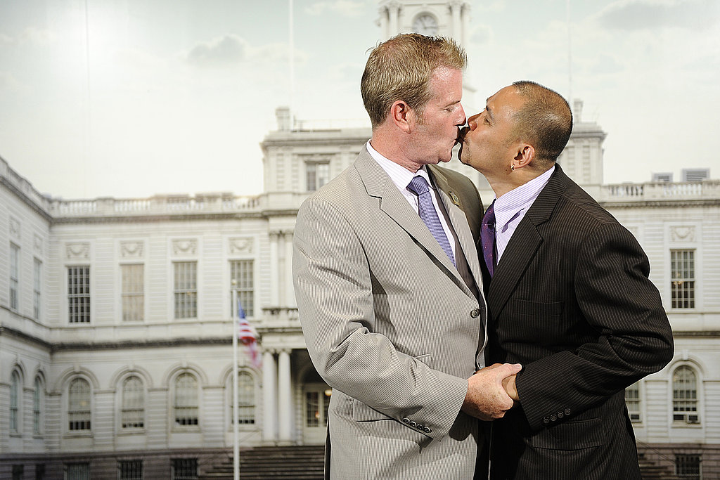 Daniel Mackey and husband Dennis Josue kiss in front of a backdrop of City Hall after their wedding ceremony at the Manhattan city clerk's office.
