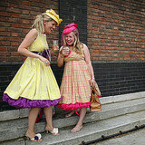 Festival-goers share a drink in vintage frocks.