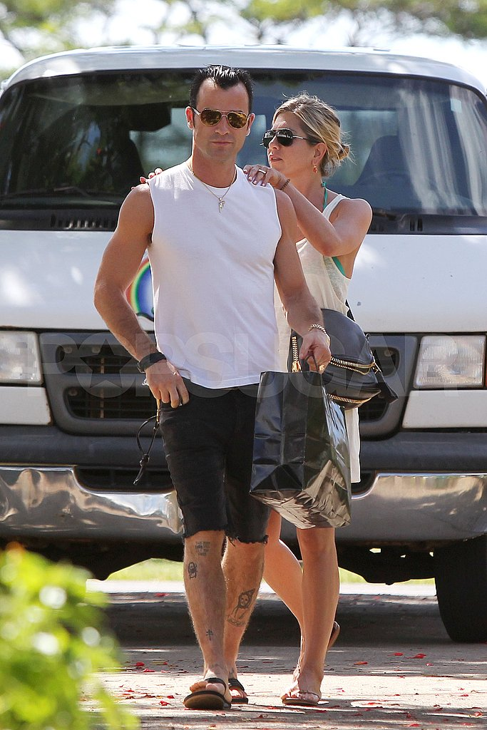 Jennifer Aniston rubs Justin Theroux's back.