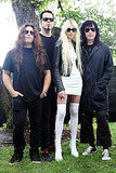 Taylor Momsen posing with her band, The Pretty Reckless, in a white mini dress, thigh-high socks, and a leather jacket.