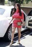 Kim Kardashian coordinated a neutral clutch, pumps, and belt with her bright pink dress.