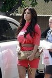 Kim Kardashian coordinated a neutral clutch and belt with her bright pink dress.