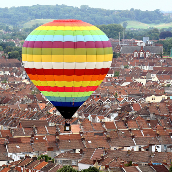 A rainbow-colored balloon brightens up the sky.