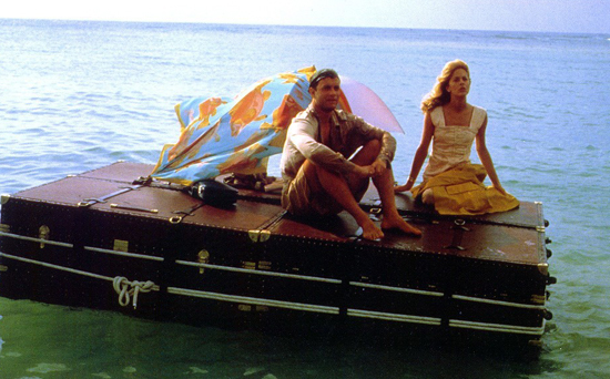 A still from the film Joe Vs. The Volcano with Tom Hanks and Meg Ryan on top of his floating luggage.
