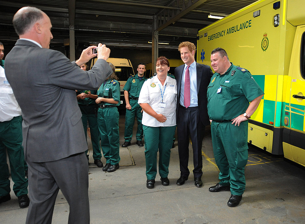 Prince Harry poses for a picture with ambulance crew members.