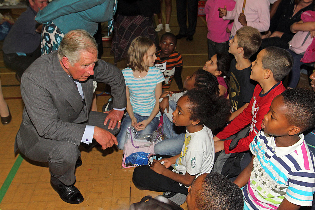 Charles gets down to greet some younger citizens impacted by the riots.