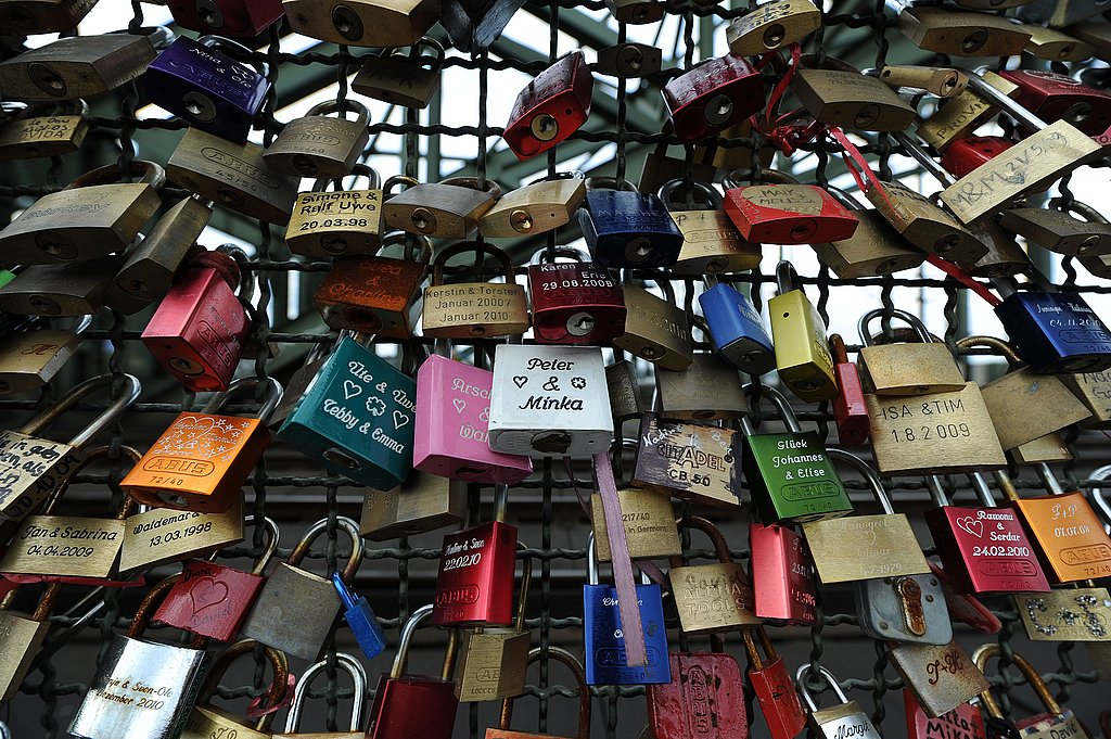 Liebesschloesser (love padlocks) are attached to a fence at the Hohenzollernbruecke bridge in Cologne, Germany.