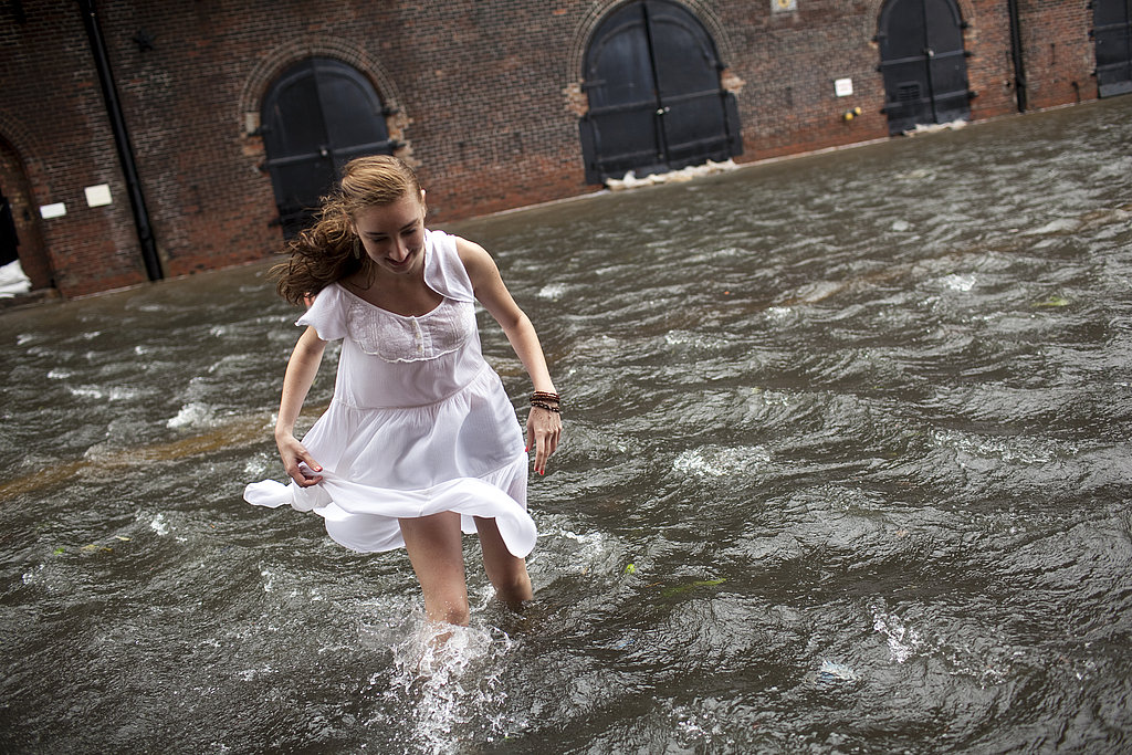 A woman walks through a flooded street in Brooklyn, NY.
