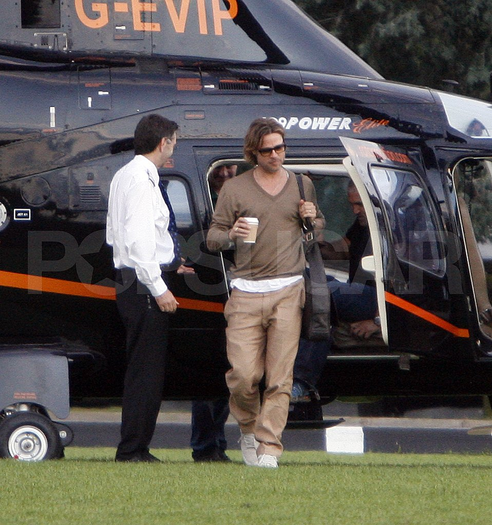 Brad Pitt hops off a helicopter.