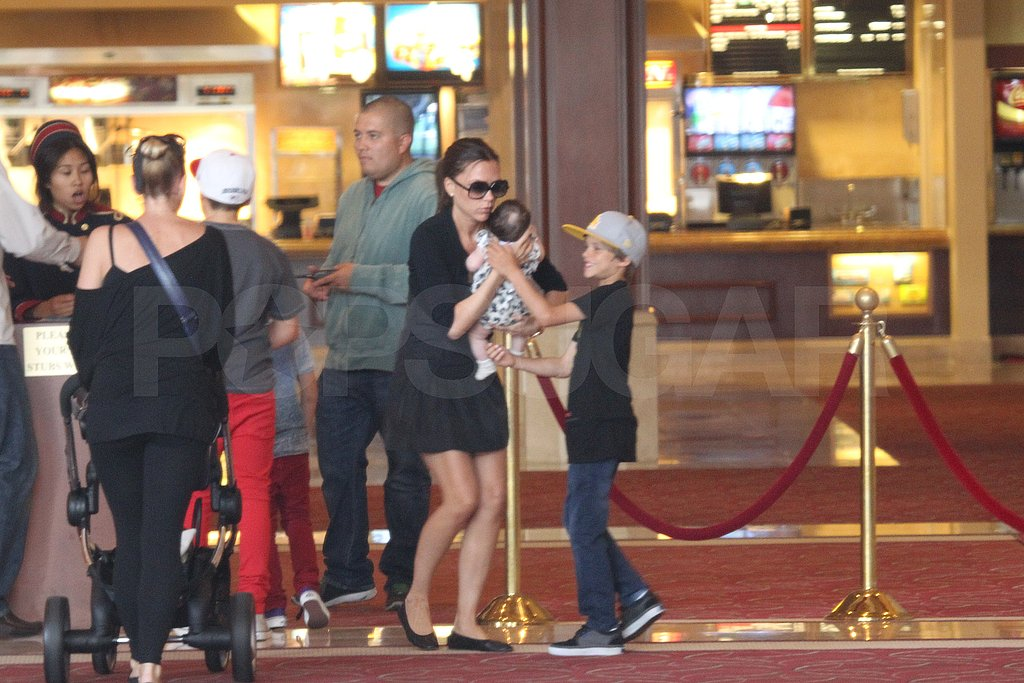 Romeo Beckham held Harper while they waited in line at the movie theater.