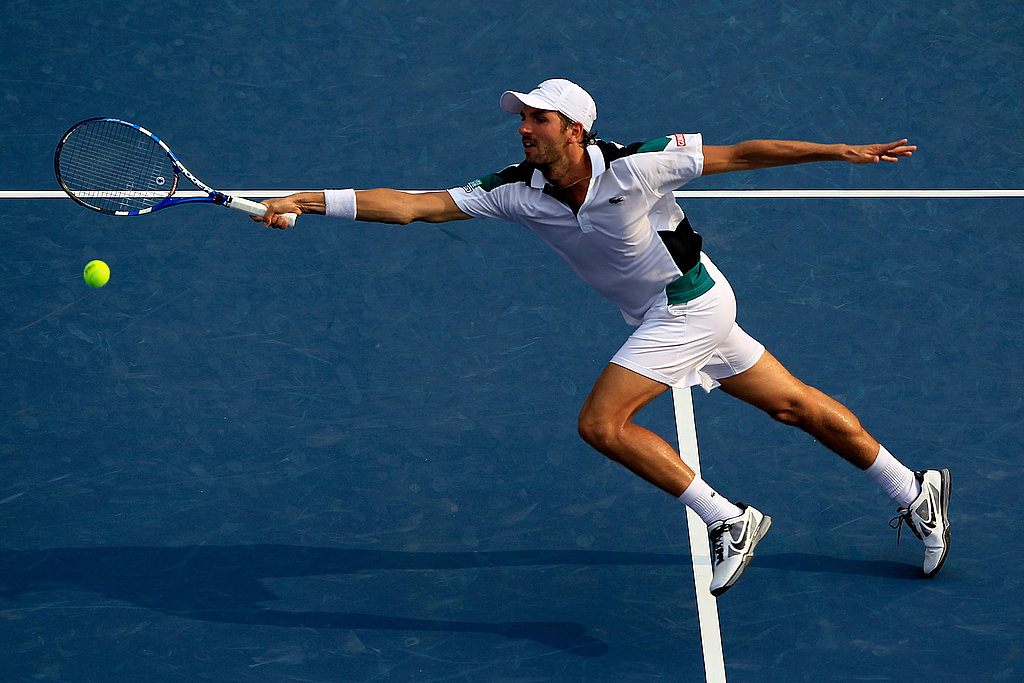 Julien Benneteau of France returns a shot against Andy Roddick.