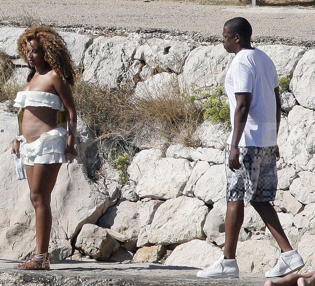 Pregnant Beyoncé Knowles in a white bikini with Jay-Z by the water.