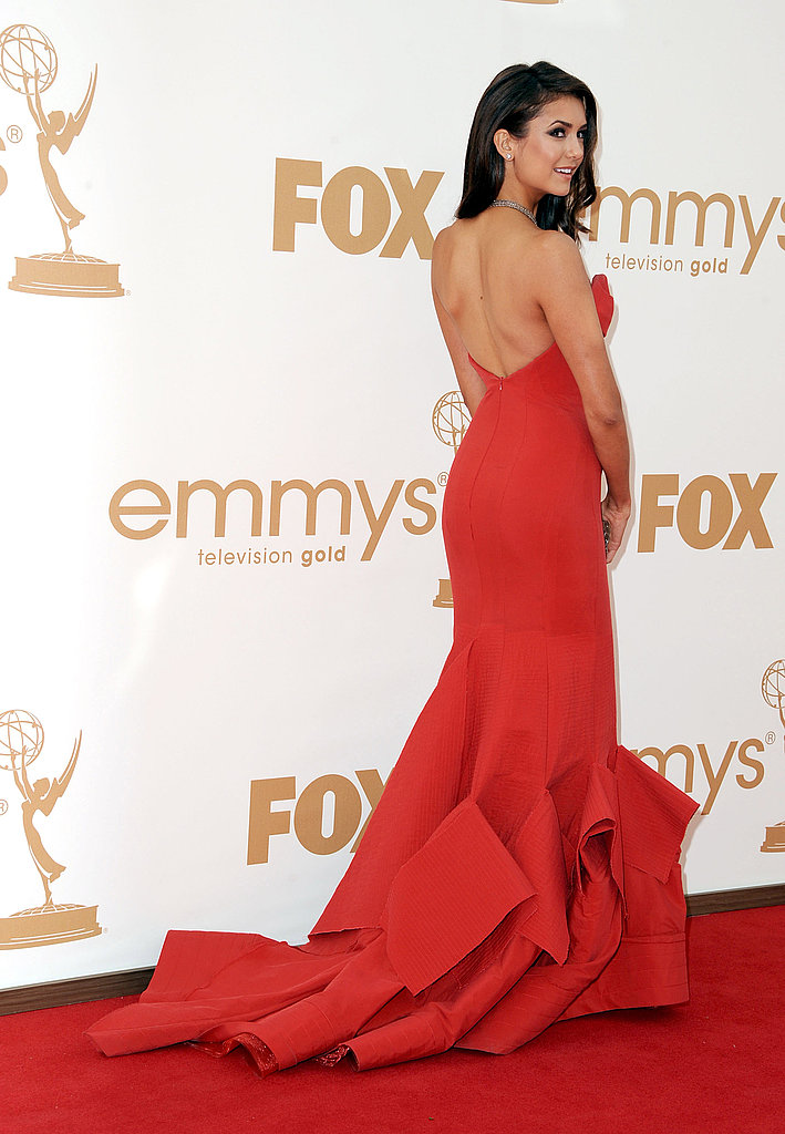 Nina Dobrev wears red, strapless Donna Karan gown.