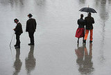 Visitors of the Oktoberfest beer festival walk through the rain at the Theresienwiese fairgrounds in Munich.