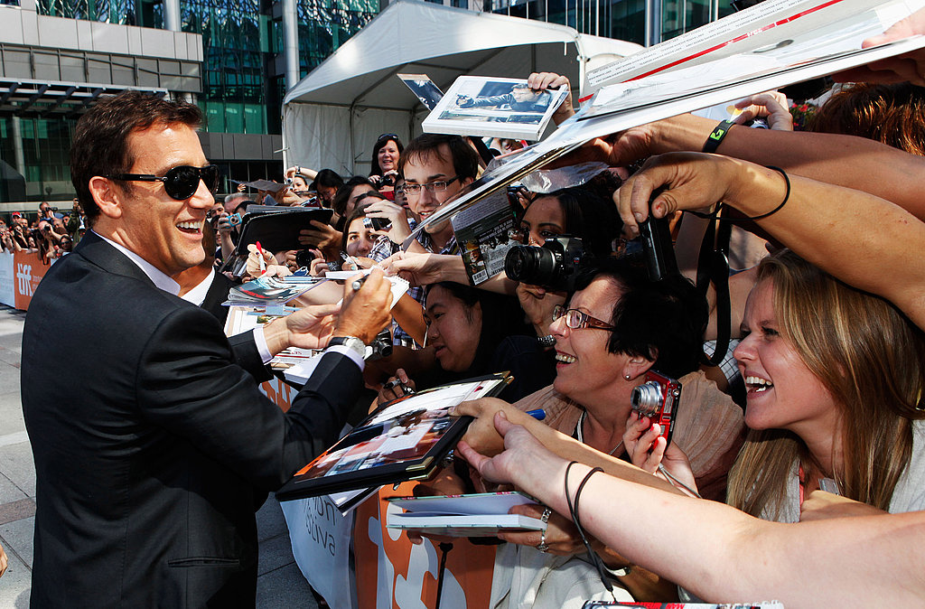 Clive Owen smiles as he signs autographs at the Killer Elite premiere.