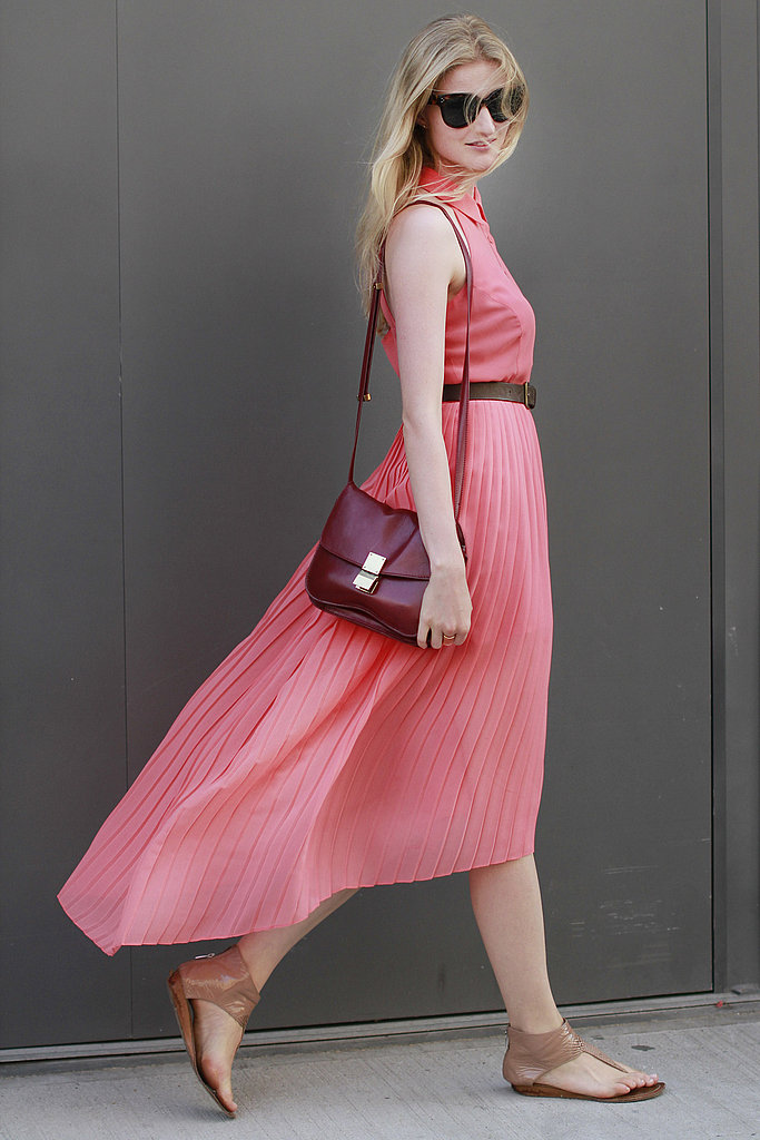 We love how this street styler worked her pink hues in a casually chic ensemble comprised of a pleated skirt, sleeveless button-up, cat-eye sunnies, red satchel, and neutral flats. Click on to get her look.