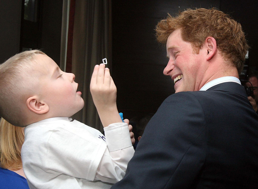 Prince Harry holds the winner of the Bravest Child Award at the WellChild Awards in 2009.
