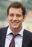 Clive Owen shows those pearly whites.