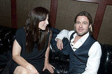 Brad Pitt and Catherine Keener talking on a leather couch.