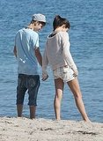 Selena and Justin held hands walking down to the water.