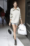 Karlie Kloss gives her denim cutoffs a cooler weather makeover with a cozy sweater and boots.