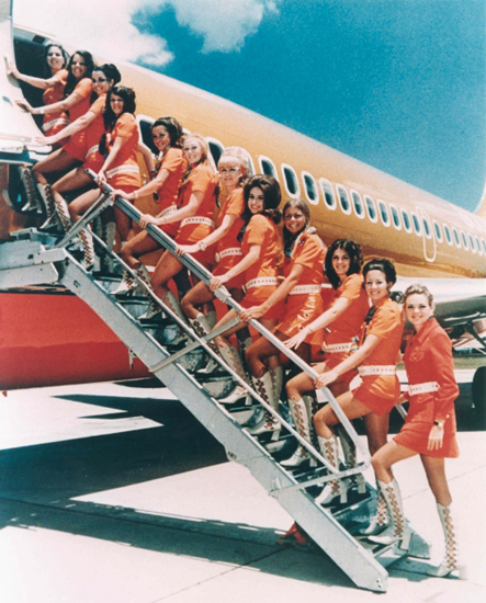 Stewardesses all in a row, looking very orange.