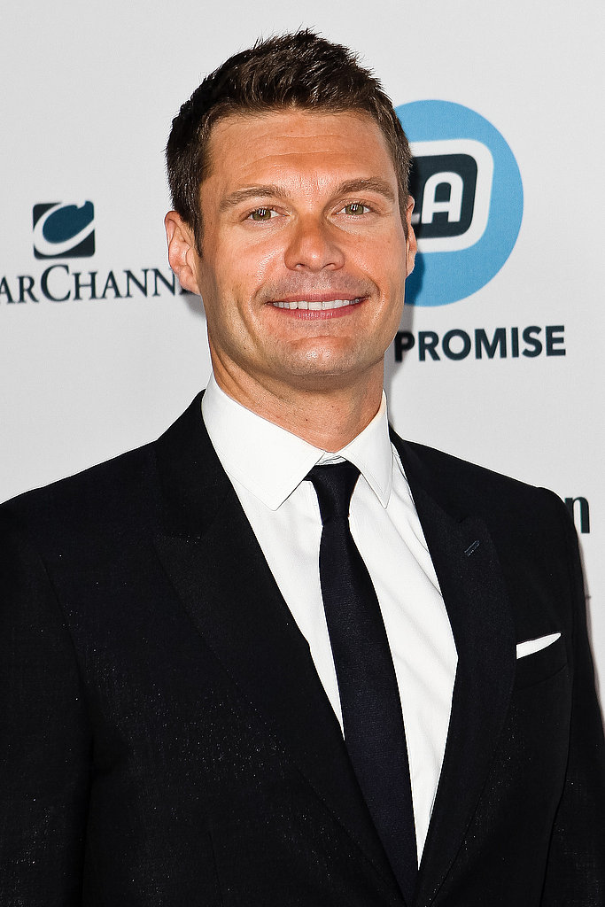 Ryan Seacrest tucked a white pocket square into his suit pocket.