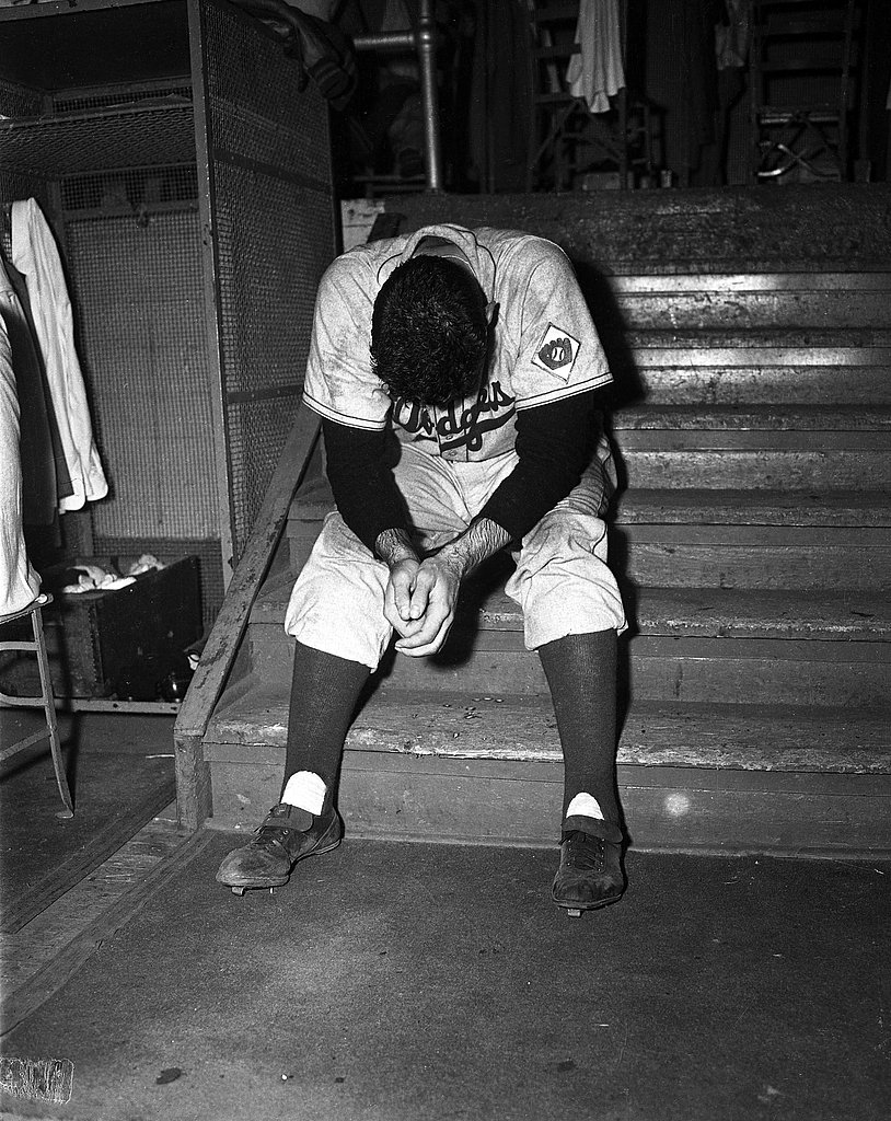 Ralph Branca sobs on Dodgers clubhouse steps after delivering the home run pitch to Bobby Thomson of the New York Giants to end pennant win hopes in 1951.