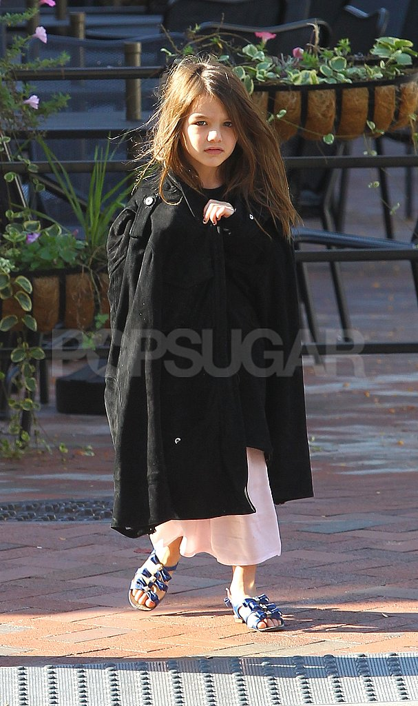 Suri Cruise wrapped a cape around herself.