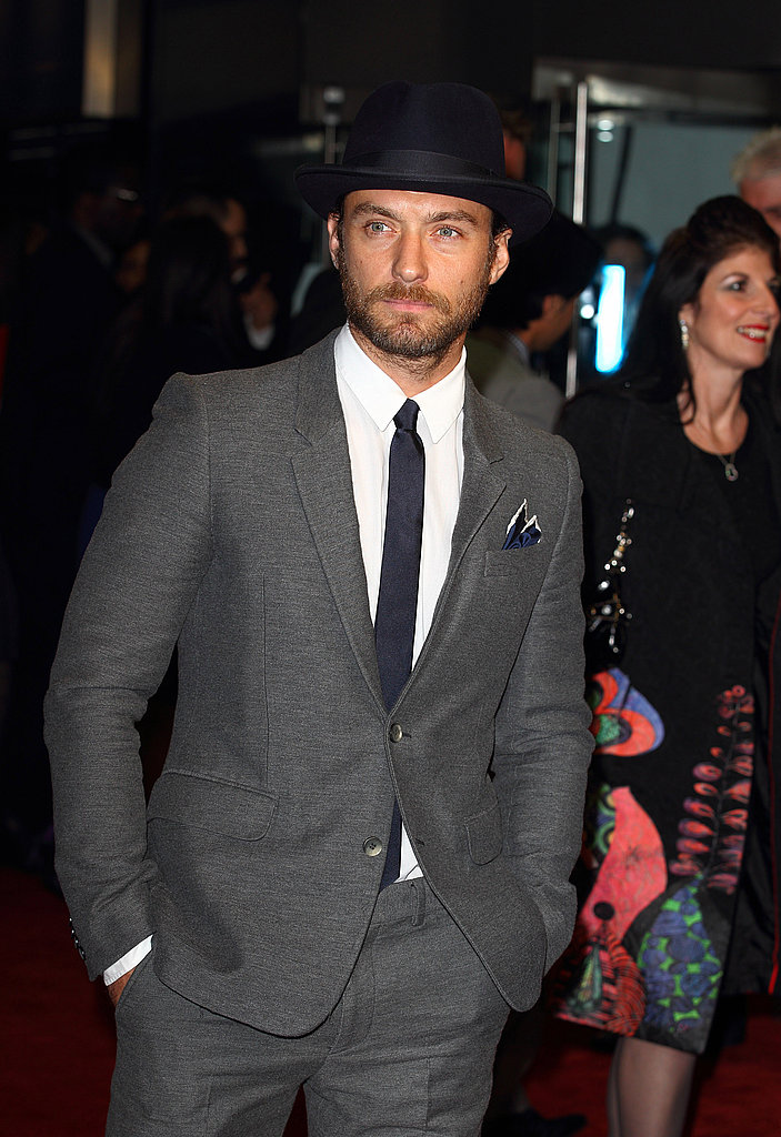 Jude Law wears a hat on the red carpet.