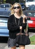 Reese paired a black bag with her chic outfit.