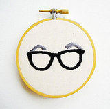 Remind your glasses-wearing cutie how specs rock by gifting mini thick-rimmed glasses embroidery art ($20).