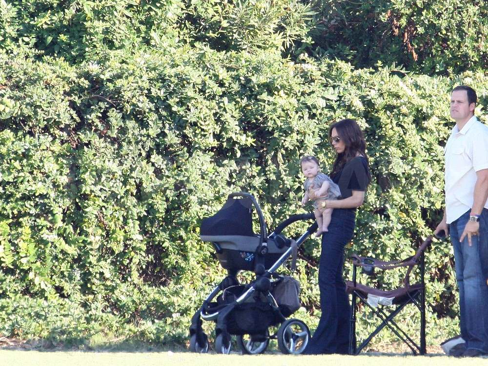 Victoria Beckham with Harper at a soccer game.