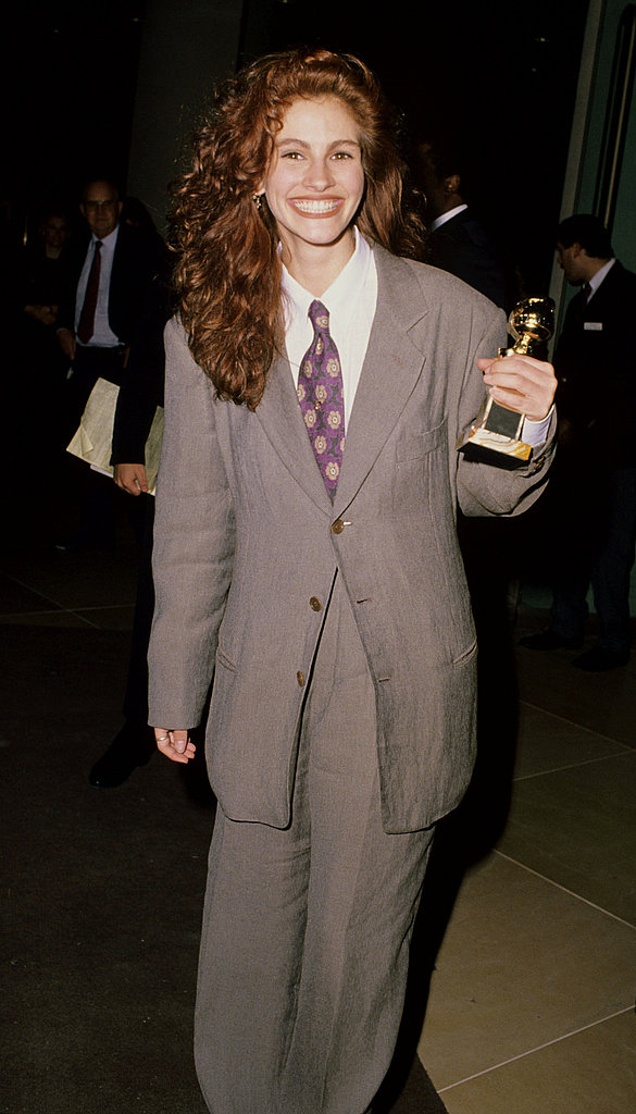 A suit-wearing Julia Roberts grinned after winning a Golden Globe in 1990.