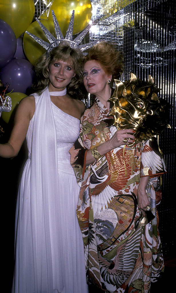 Actress Arlene Dahl's daughter Carole Holmes is an elegant statue of liberty in her all-white ensemble at a NYC Halloween party in 1985.