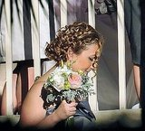 One of Eva's bridesmaids carries her bouquet.