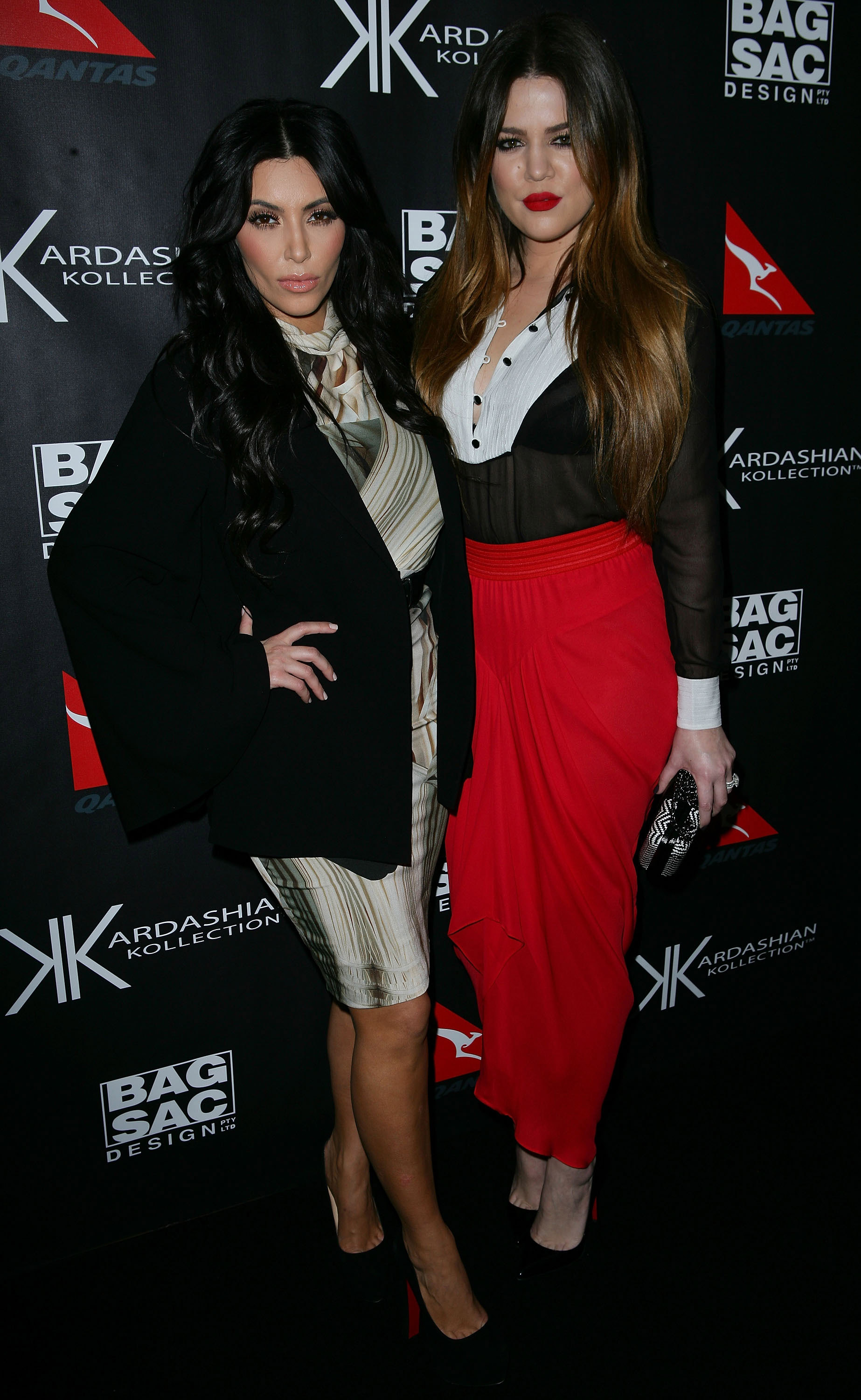 Kim and Khloe Kardashain posed together on the black carpet.